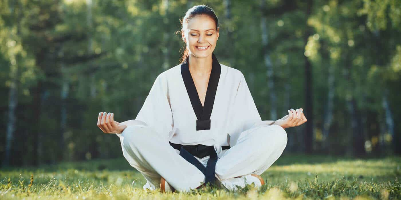 Martial Arts Lessons for Adults in Cypress TX - Happy Woman Meditated Sitting Background